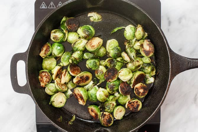 Brussels Sprouts being cooked in a skillet