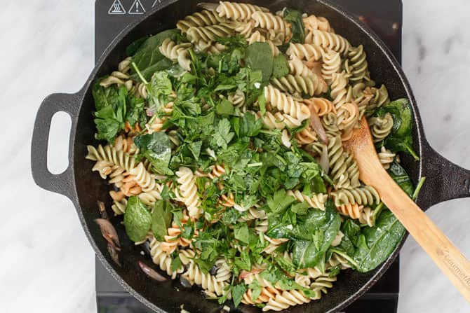 Pasta, spinach, parsley, and butternut squash combined in the skillet