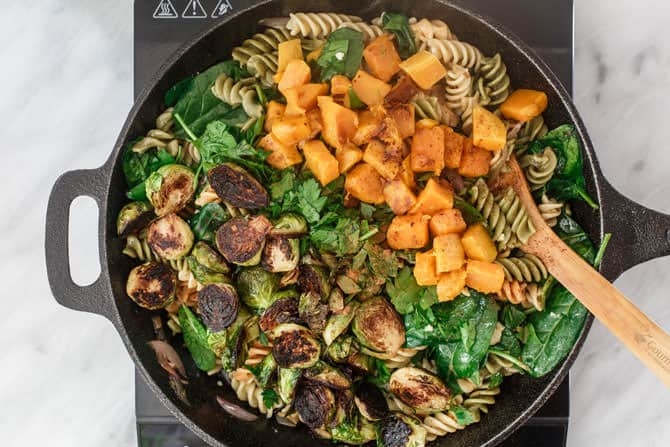 Ingredients of pasta salad combined in a skillet