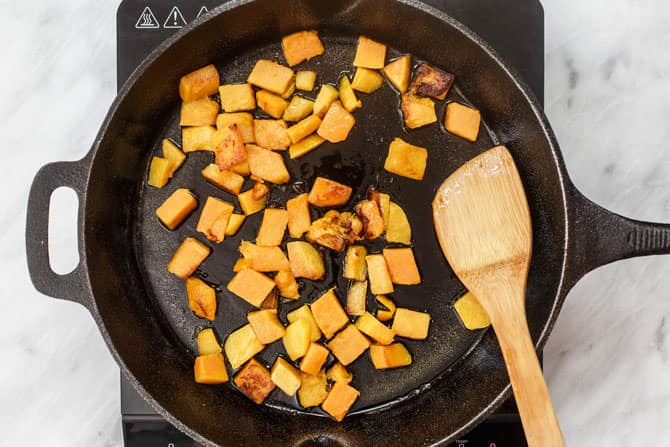 Butternut squash being cooked in a skillet