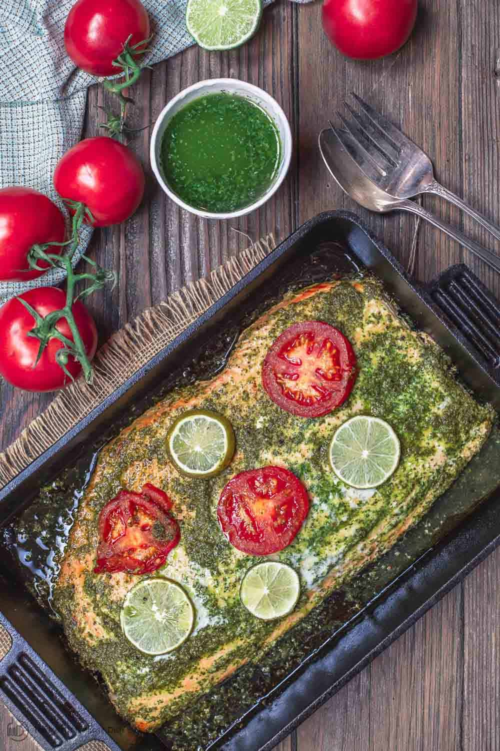 Baked Salmon served with extra garlic cilantro sauce and sliced limes