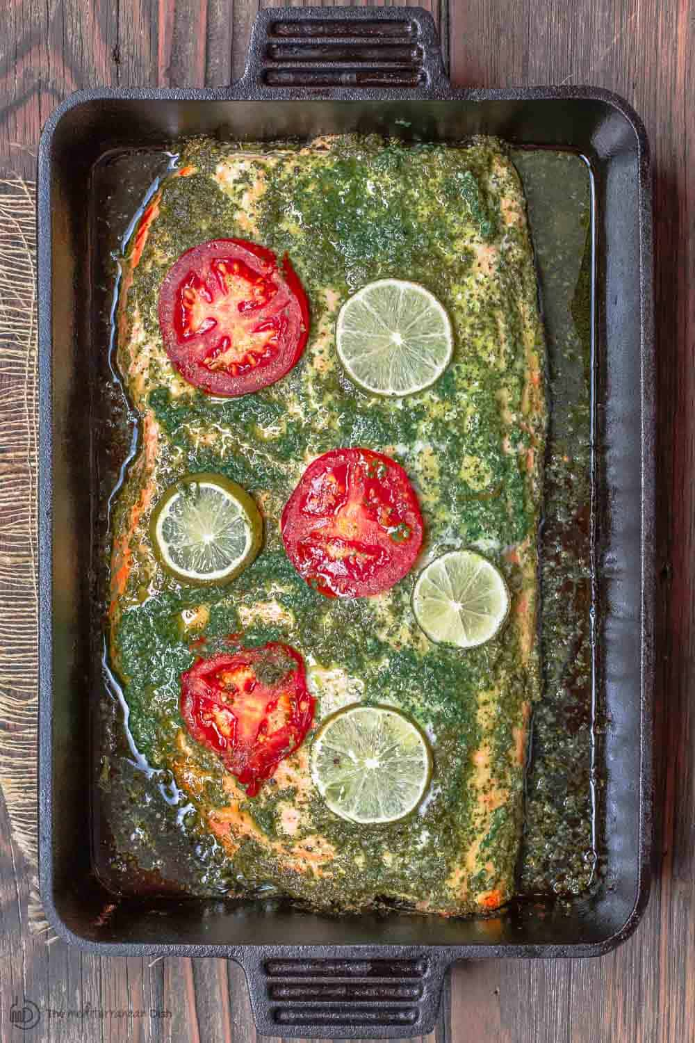 Baked Salmon garnished with tomatoes and lime slices