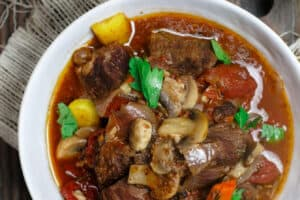 Crock Pot Italian Beef Stew Recipe | The Mediterranean Dish. This is a family favorite! Beef stew that's been slow cooked to tender perfection in a special wine broth with loads of carrots, mushrooms and aromatics. Packed with flavor from garlic, onions, and fresh herbs. Best part, it takes only 15 minutes to prep, and the crock pot does all the heavy lifting. This is the prefect beef stew! A must-try from TheMediterraneanDish.com