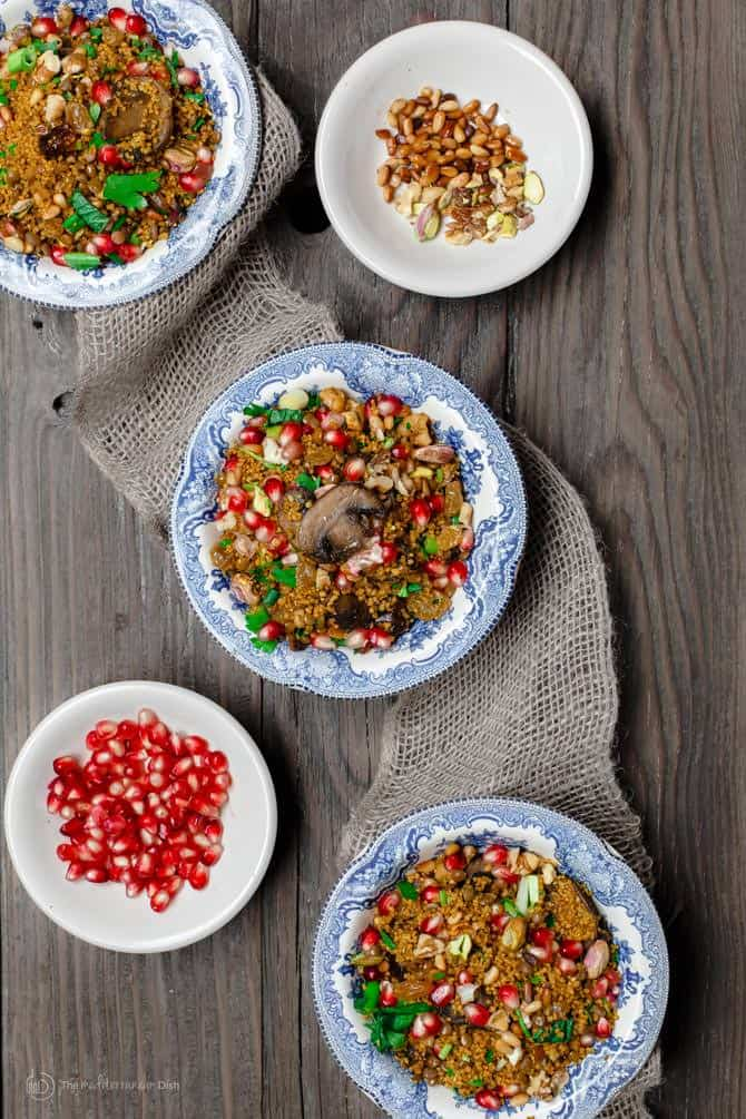 Individual servings of the jeweled couscous dish. Extra pomegranate seeds and nuts served on the side for additional texture.