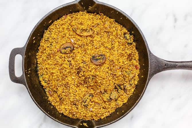 Skillet containing couscous, mushrooms, garlic, onions, spices, and the mixture of pomegranate molasses, lemon juice and olive oil.