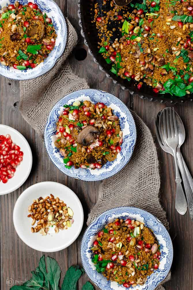Couscous topped with pomegranate seeds and lentils. Side of extra pomegranate seeds and nuts for additional texture.