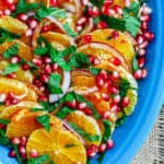 Easy Mediterranean Orange and Pomegranate Salad | The Mediterranean Dish. A simple, bright and refreshing orange and pomegranate salad with a little red onion and fresh mint. A honey dressing on top brings it all together! Perfect for holiday dinners or any day next to meaty or fish entrees. Get the recipe on The MediterraneanDish.com