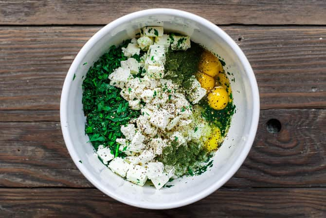Spanakopita filling ingredients in a bowl. Spinach, feta, fresh herbs, onions, garlic and eggs