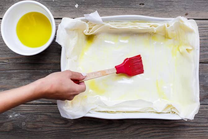 Phyllo sheets being brushed with olive oil