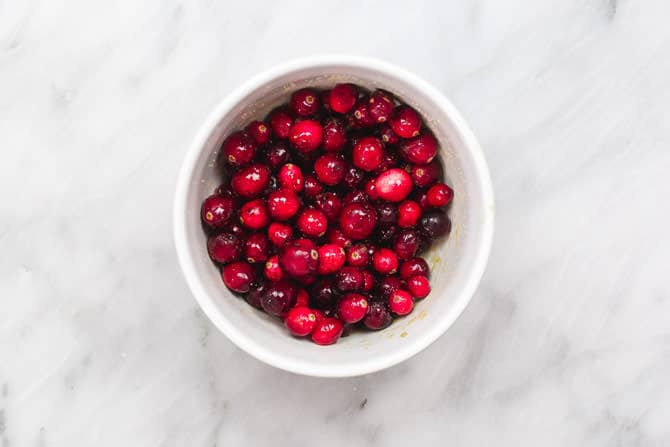 fresh cranberries marinating in a bowl with brown sugar and vinegar