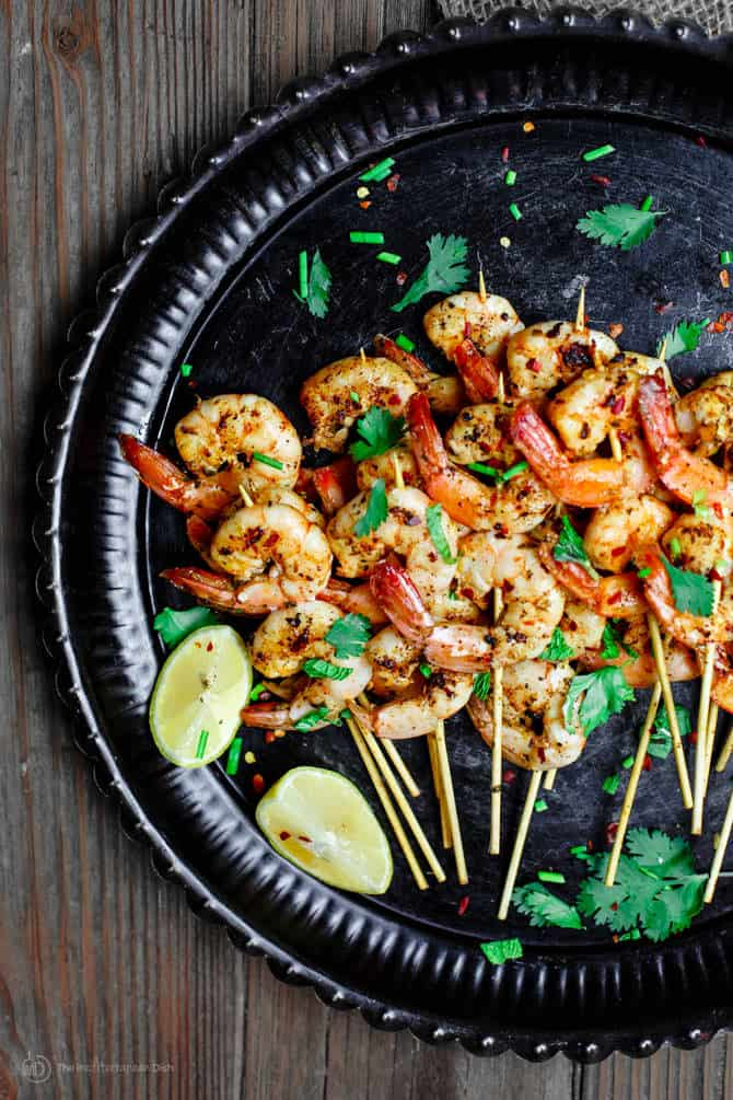 Skewers of shrimp served on a plate with lemon wedges