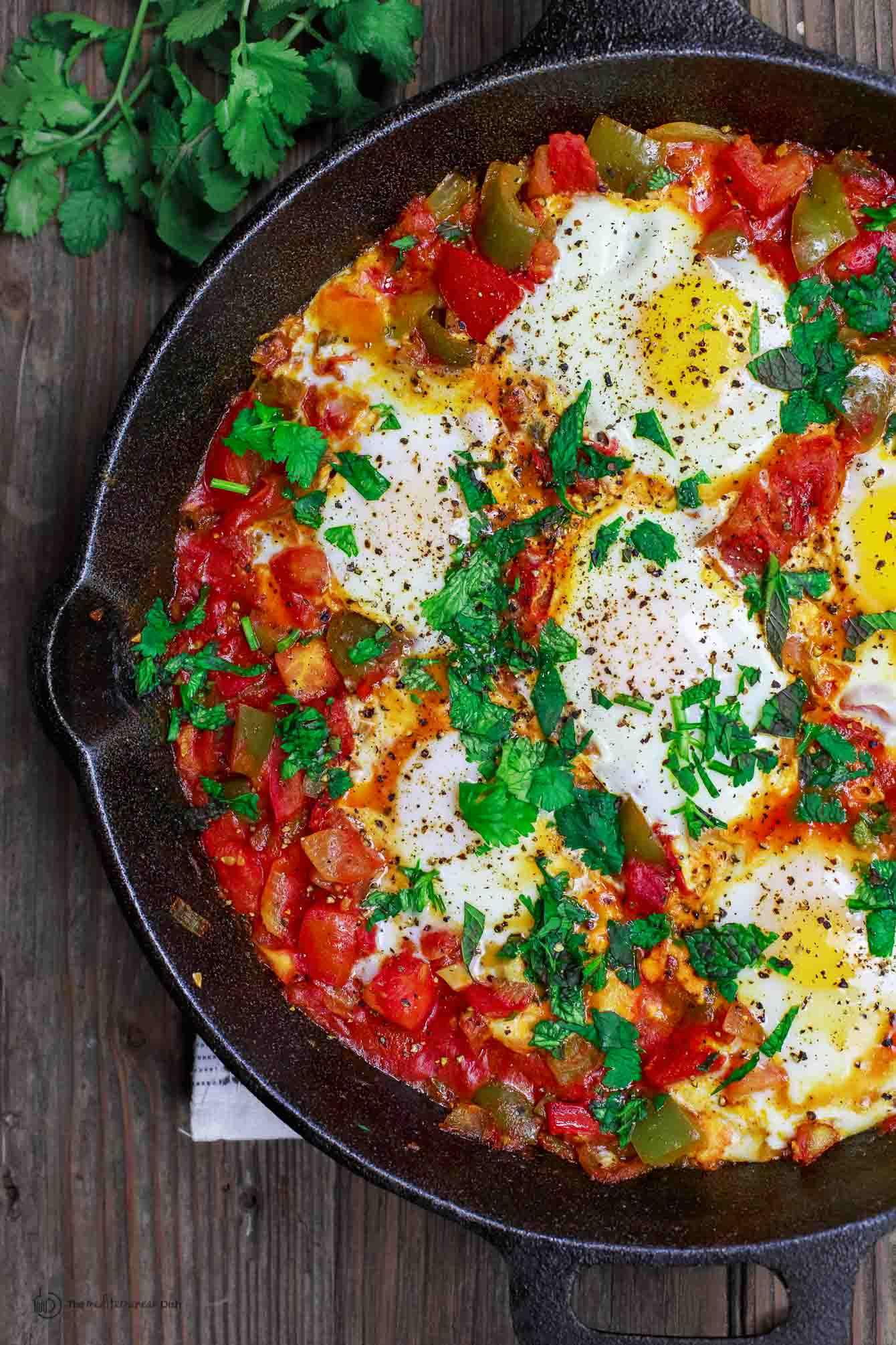 Simple Shakshuka in skillet. Poached eggs in a tomato and bell pepper stew.