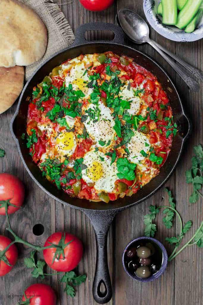 Shakshuka eggs in cast iron skillet with pita bread and sides of cucumbers and olives