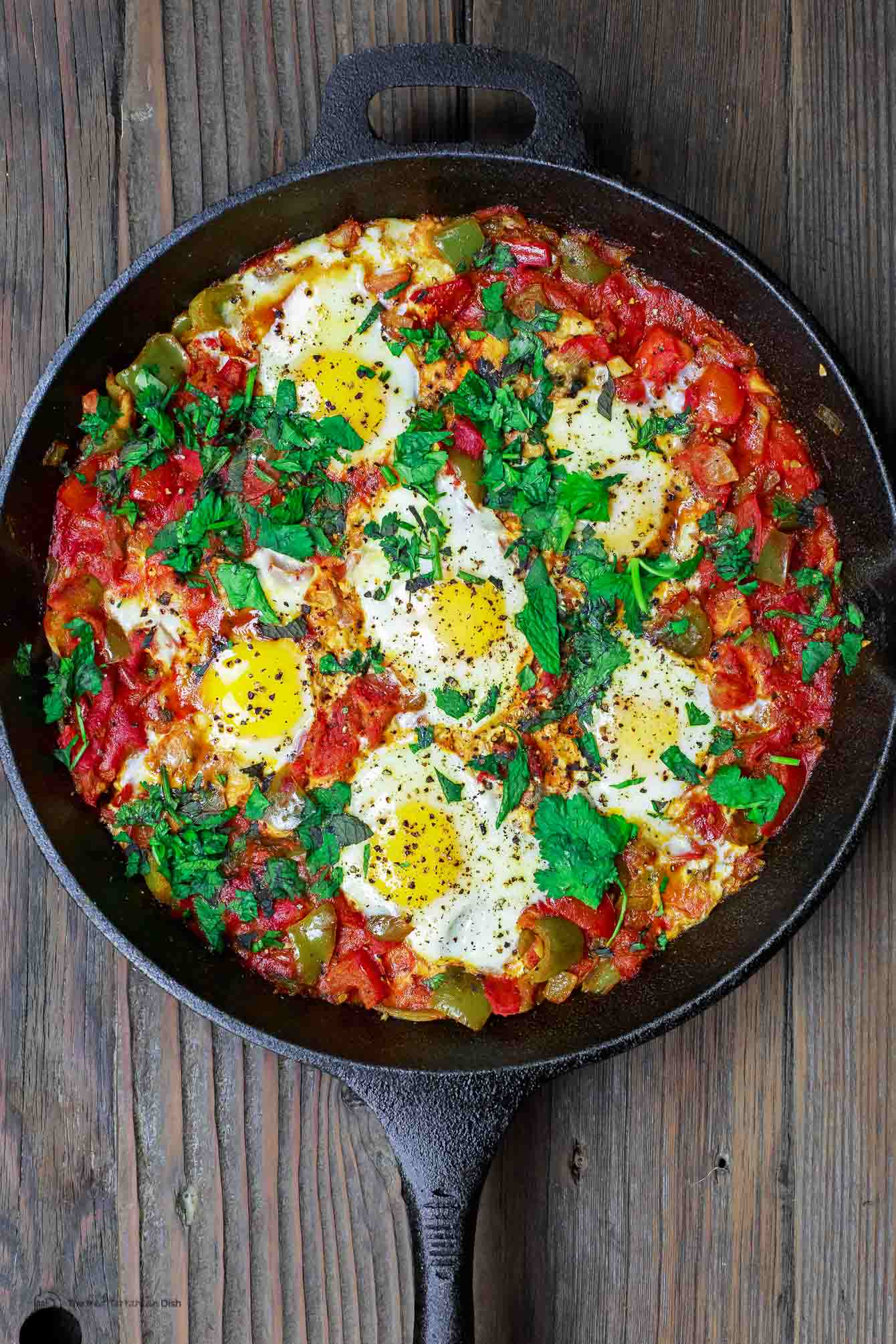 Simple Shakshuka Recipe | The Mediterranean Dish. Shakshuka is a delicious Middle Eastern dish of eggs poached in a spiced, saucy tomato stew. Perfect for breakfast, lunch or dinner! All you need to add is your favorite bread. This is a simple vegetarian recipe that you can make in less than 30 minutes! My family's favorite. And feeds a crowd on a small budget. See the recipe on TheMediterraneanDish.com