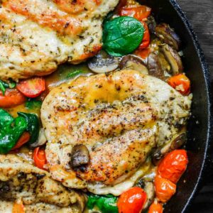 30-Minute Italian Skillet Chicken Recipe with Tomatoes and Mushrooms | The Mediterranean Dish. Flavor packed chicken breasts cooked in white wine with mushrooms, tomatoes and more! The perfect weeknight dinner in minutes! See the recipe on TheMediterraneanDish.com