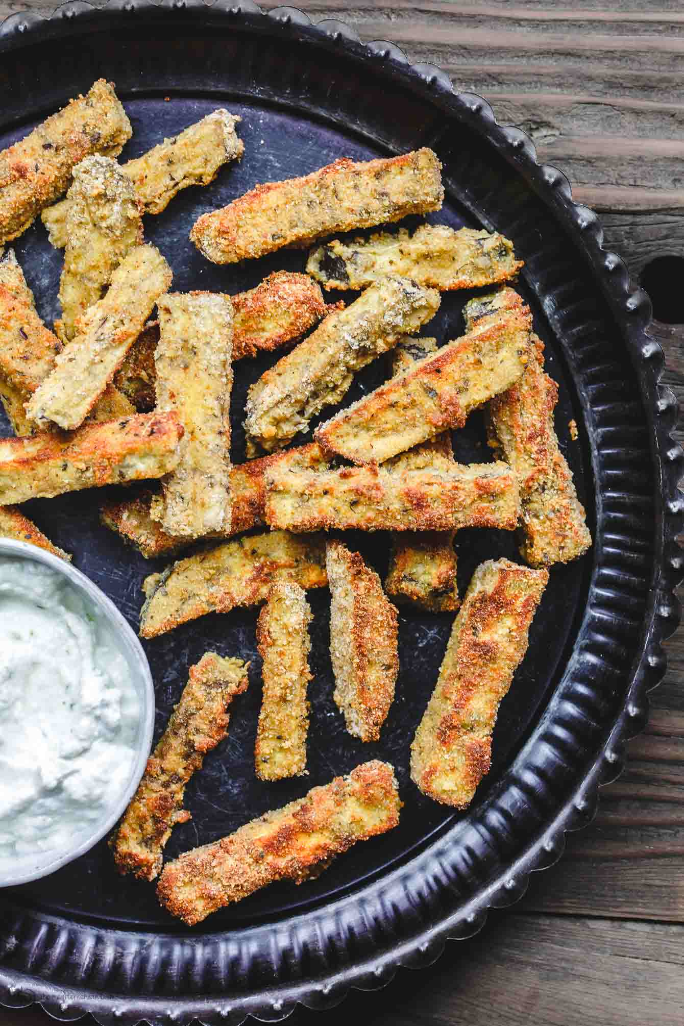 Plate with crispy, baked eggplant fries served with Greek Tzatziki Sauce