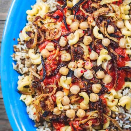 Egyptian Koshari Recipe | The Mediterranean Dish. Hands down a family favorite. A comforting bowl of spiced lentils and rice with chickpeas, tiny pasta, and tomato sauce. Topped with thin crispy onion rings. A tasty, budget friendly, vegan recipe! See it on TheMediterraneanDish.com