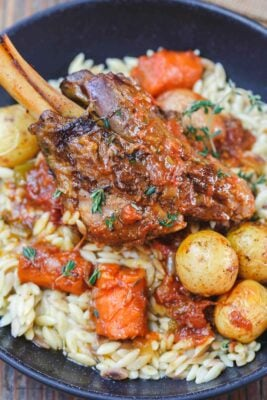 Mediterranean-Style Wine Braised Lamb Shanks Recipe | The Mediterranean Dish. Braising and slow cooker instructions included! Spiced lamb shanks cooked in a red wine and tomato sauce with vegetables, aromatics and fresh herbs! A family favorite for Easter or your next special dinner! See it on TheMediterraneanDish.com