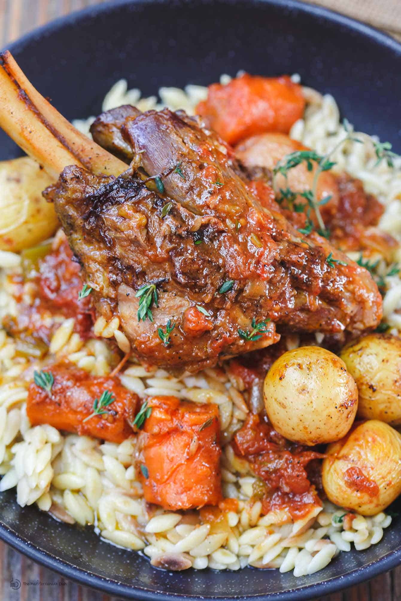 Close-up of Wine Braised Lamb Shanks served over rice and vegetables