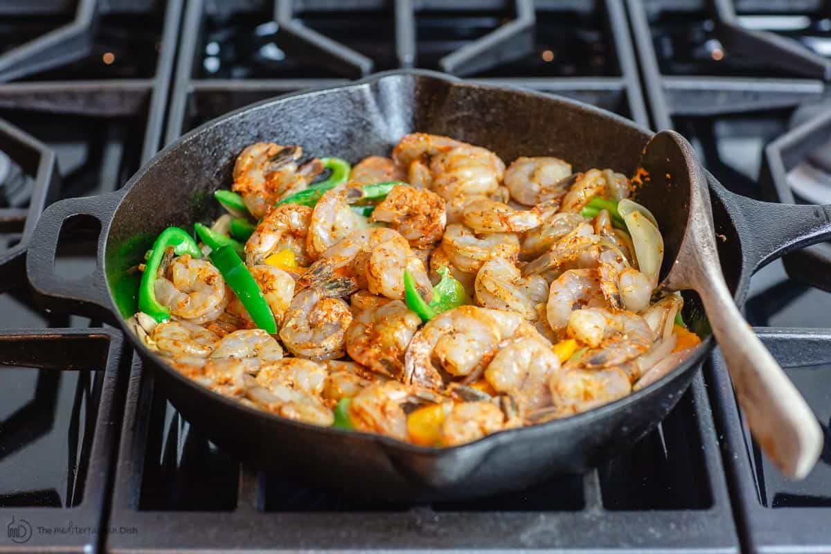 Shrimp is added to cook with bell peppers, shallots and garlic