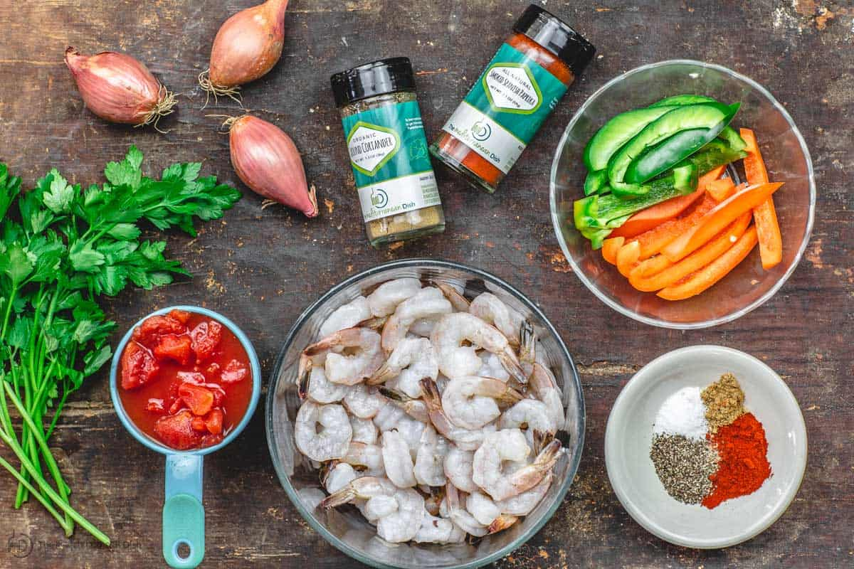 Ingredients for shrimp recipe including shrimp, spices, bell peppers, tomatoes and parsley