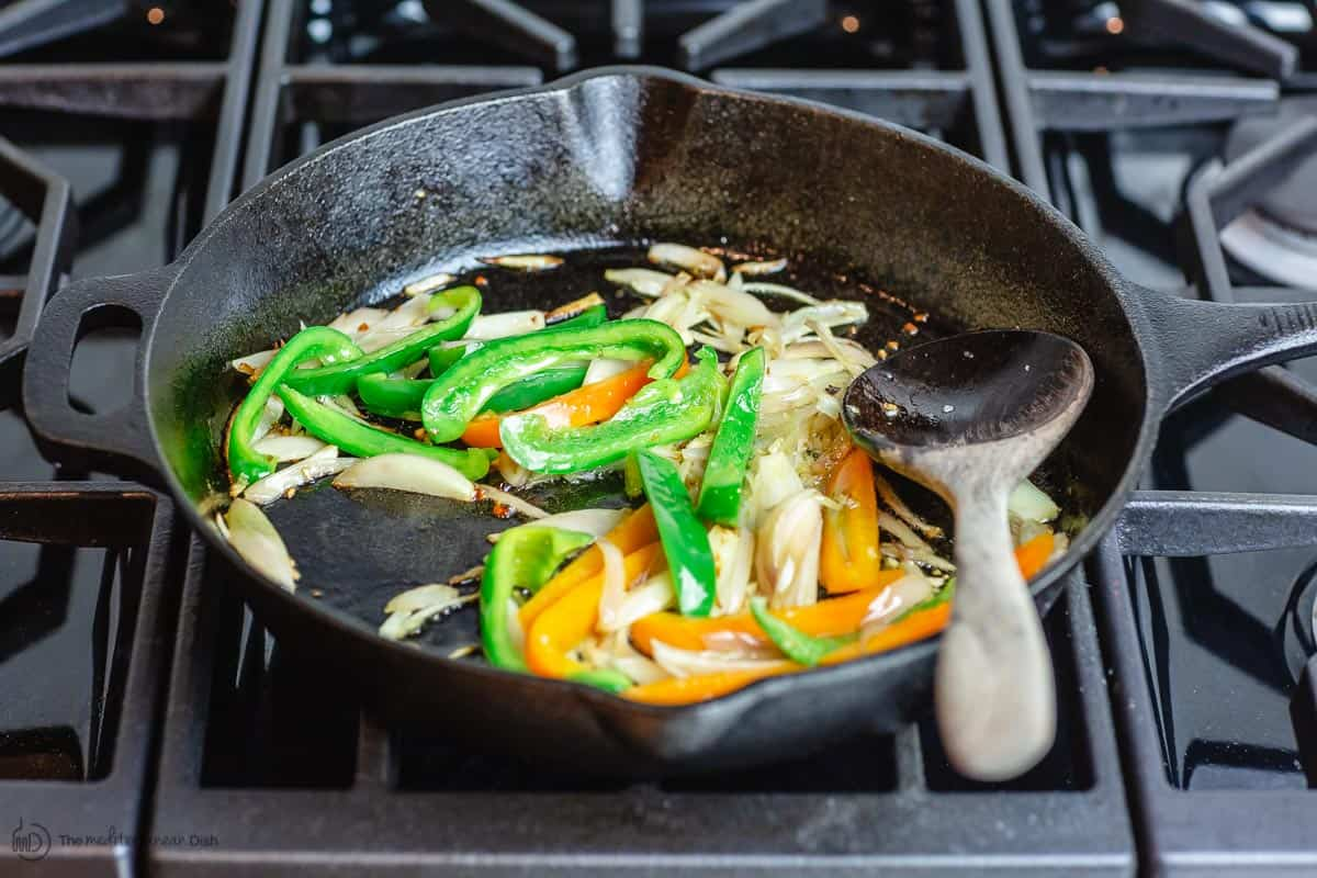 Bell peppers are added to cook with shallots and garlic
