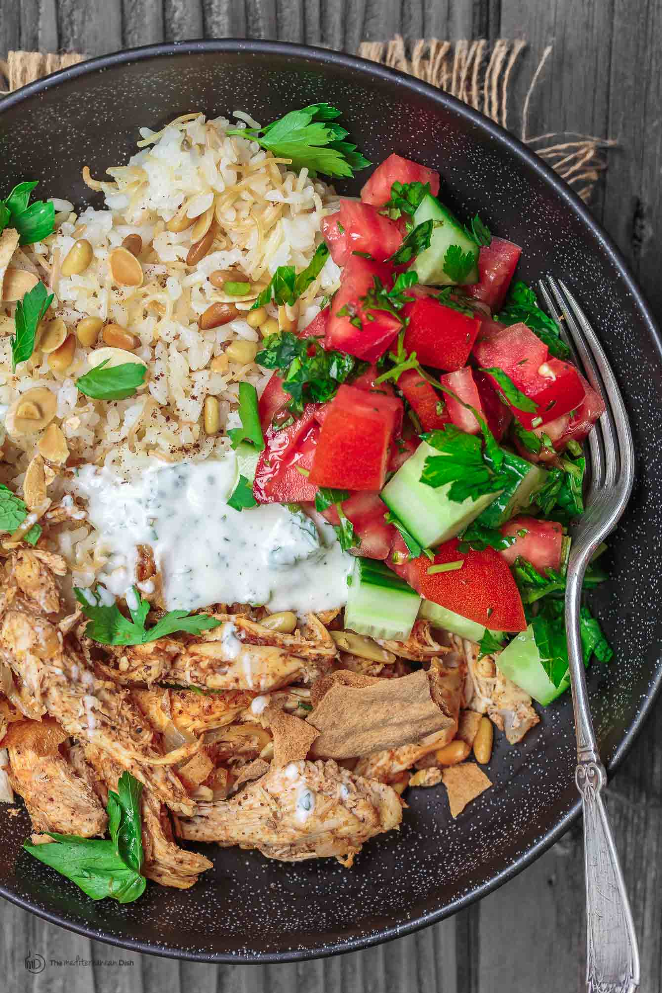 Chicken Fatteh served in a bowl topped with mint dip sauce