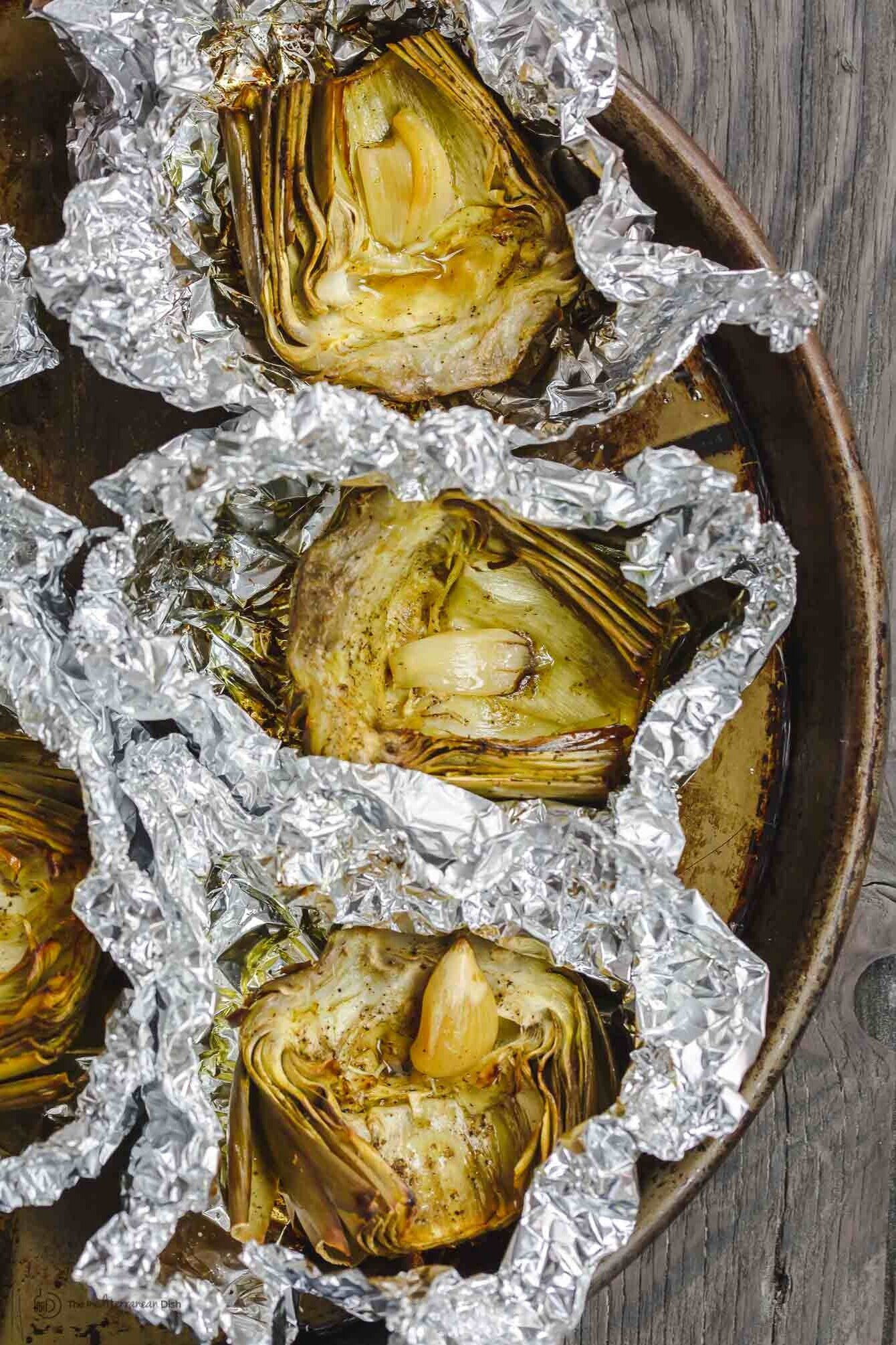 roasted artichoke halves in foil with garlic in the middle
