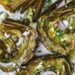 Mediterranean-style roasted artichokes topped with shallots, feta, capers, and dill
