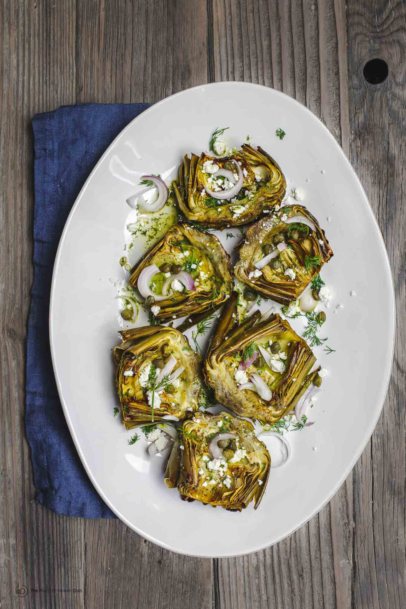 Plated artichokes garnished with feta cheese, capers and onions