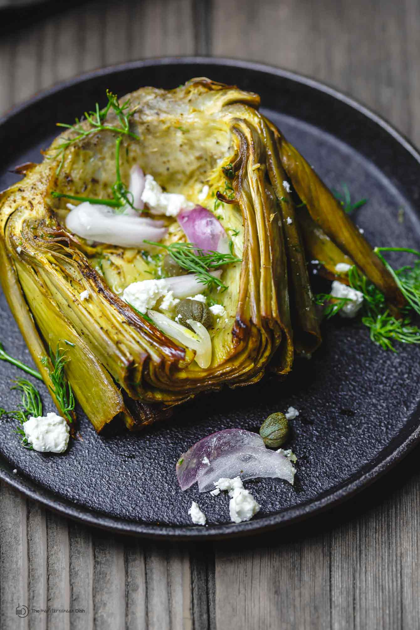 One serving of roasted artichoke on plate to be served.