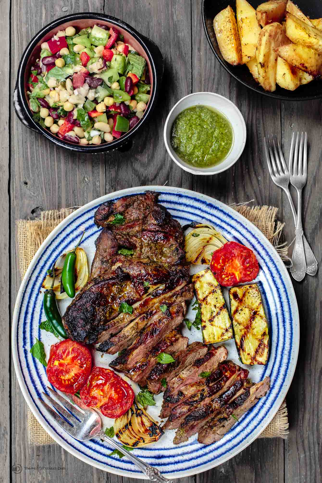 Mediterranean Grilled Lamb Recipe with Mint Pesto | The Mediterranean Dish. Garlic-herb marinated leg of lamb, tenderized and grilled to perfection! Plus mint pesto or Greek Tzatziki sauce and favorite Mediterranean summer sides and salads! See it on TheMediterraneanDish.com