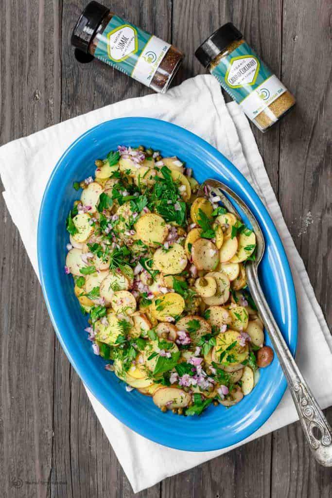 Mediterranean mustard potato salad on platter. Two spice bottles to the side