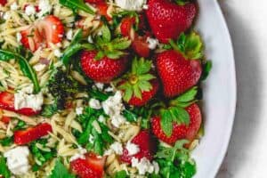 Mediterranean Strawberry Orzo Pasta Salad | The Mediterranean Dish. BEST orzo salad you will have! Packed with Mediterranean flavors from fresh herbs, lemony vinaigrette and feta cheese. A must try! See it on TheMediterraneanDish.com