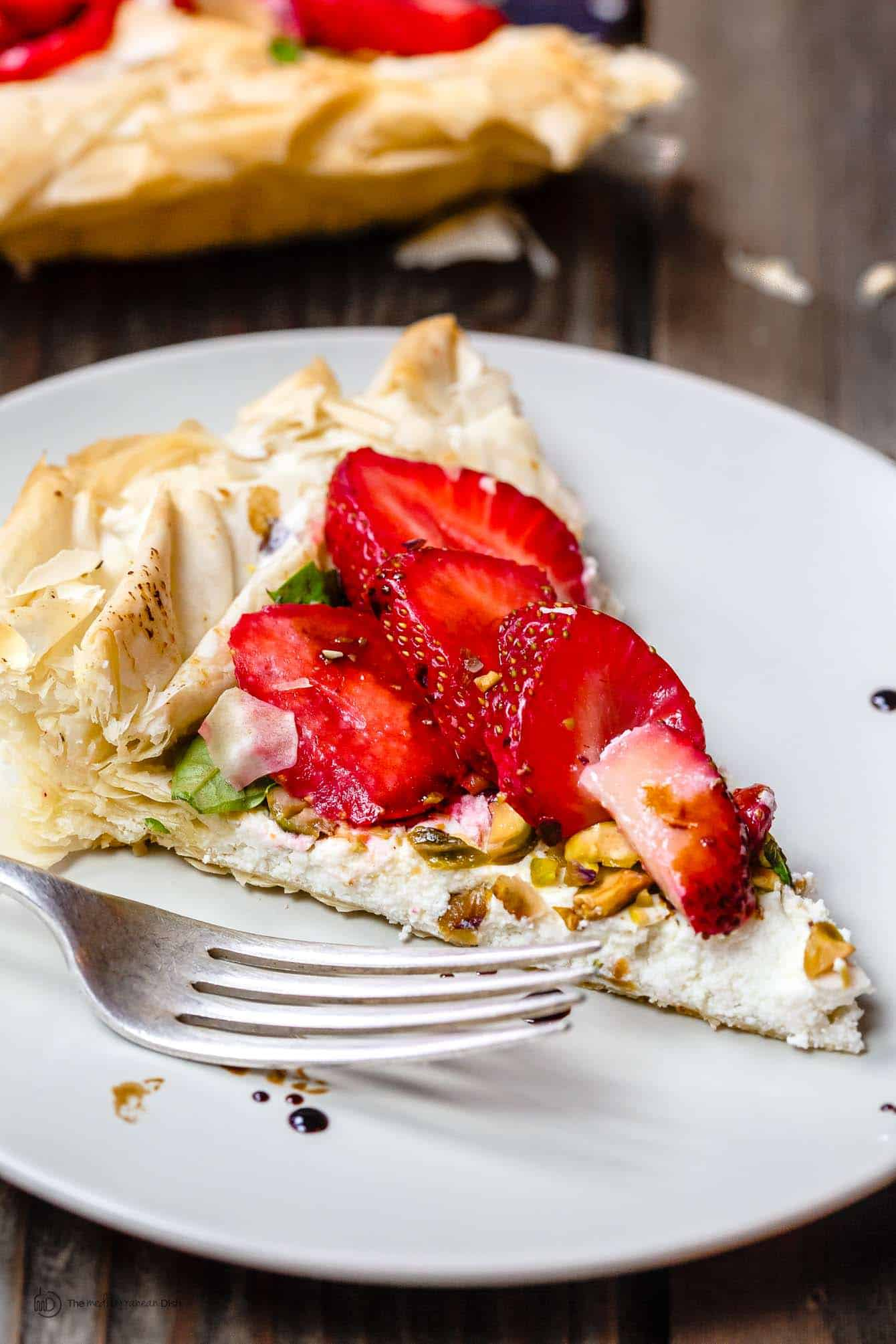 Slice of Strawberry Tart garnished with crushed nuts