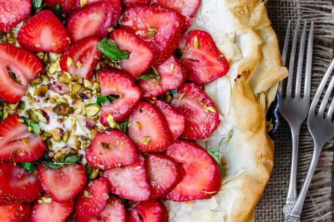 Feta Strawberry Tart with Fillo Crust | The Mediterranean Dish. A gorgeous sweet and savory strawberry tart with feta cheese, pistachio, basil and balsamic reduction! The flaky fillo (phyllo) crust takes it to a whole level of tasty! Easy recipe with step-by-step tutorial from TheMediterraneanDish.com