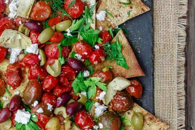 Mediterranean Roasted Tomato Nachos Recipe | The Mediterranean Dish. Homemade crispy nachos made with light, healthy flatbread. Loads of garlic roasted tomatoes and Mediterranean favorites on top! The perfect appetizer or little mezze dish!