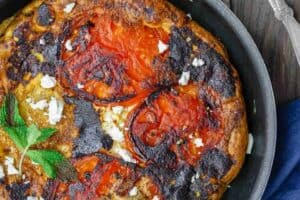 Open-Faced Greek Omelet Recipe with Tomatoes | The Mediterranean Dish. A simple Greek omelet or Fritatta with tomatoes, a sprinkle of feta cheese, fresh mint and favorite Mediterranean spices. This Greek omelet makes an excellent quick vegetarian dinner as well! See the recipe on TheMediterraneanDish.com