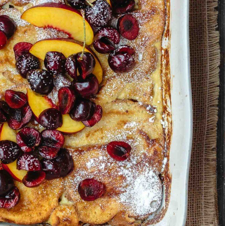 Overnight Baked French Toast Recipe with Challah | The Mediterranean Dish. Stupid easy and healtiher overnight french toast! Challah french toast with a reduced-fat yogurt custard, topped with fresh fruit and honey simple syrup. Prep it overnight and come morning, simply slip into the oven and enjoy your coffee!