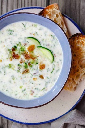 Persian Chilled Cucumber Soup (Abdoogh Kiar) | The Mediterranean Dish. A cold cucumber soup in a yogurt base with lots of fresh herbs, toasted walnuts, and raisins. Think detox soup to help you cool off and rest your body! See the recipe on TheMediterraneanDish.com