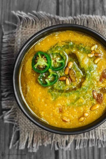 Vegan Pumpkin Soup in serving bowl. Topped with spicy cilantro pesto and jalapenos