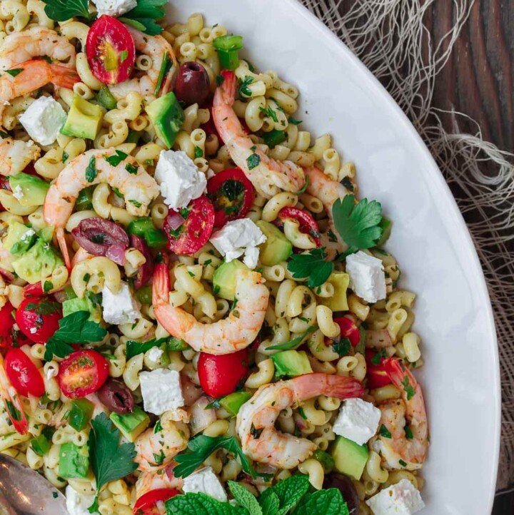 Mediterranean Pasta Salad | The Mediterranean Dish. Easy shrimp and avocado Mediterranean pasta salad. A light and zesty Mediterranean dressing, and tons of fresh herbs, chopped veggies, olives and more, take this shrimp pasta salad to a new level of delicious! See the full recipe on TheMediterraneanDish.com. #pastasalad #mediterraneanrecipe #mediterraneandiet #shrimppastasalad