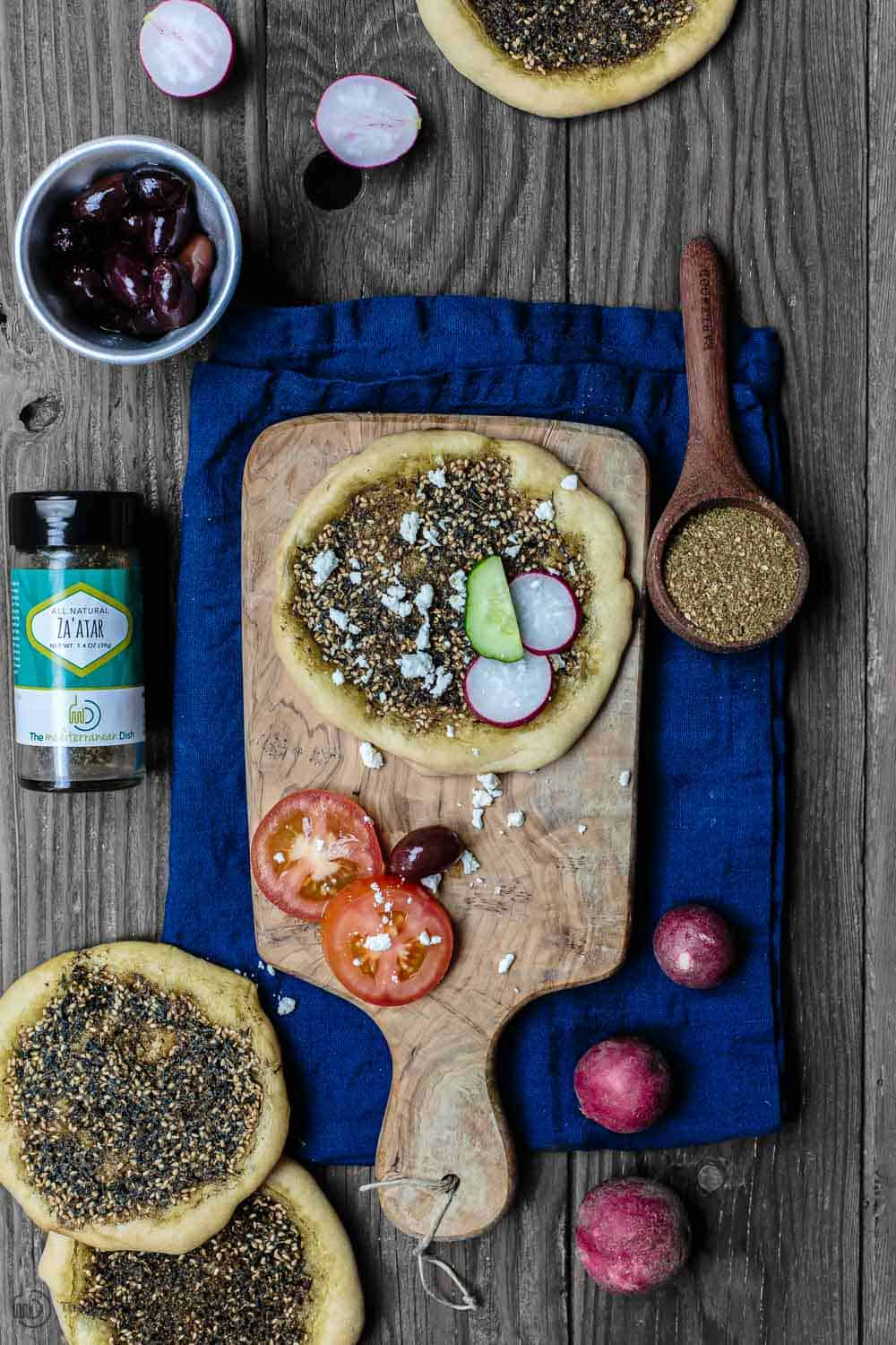 Za'atar Manaqish (Manakish) Recipe | The Mediterranean Dish. Middle Eastern homemade flatbread with olive oil and Za'atar spice. Easy vegan recipe that's perfect for snack, appetizer, or even brunch. See the full recipe on TheMediterraneanDish.com #mediterraneandiet #mediterraneanrecipe #mediterraneandietrecipe #manakish #flatbread
