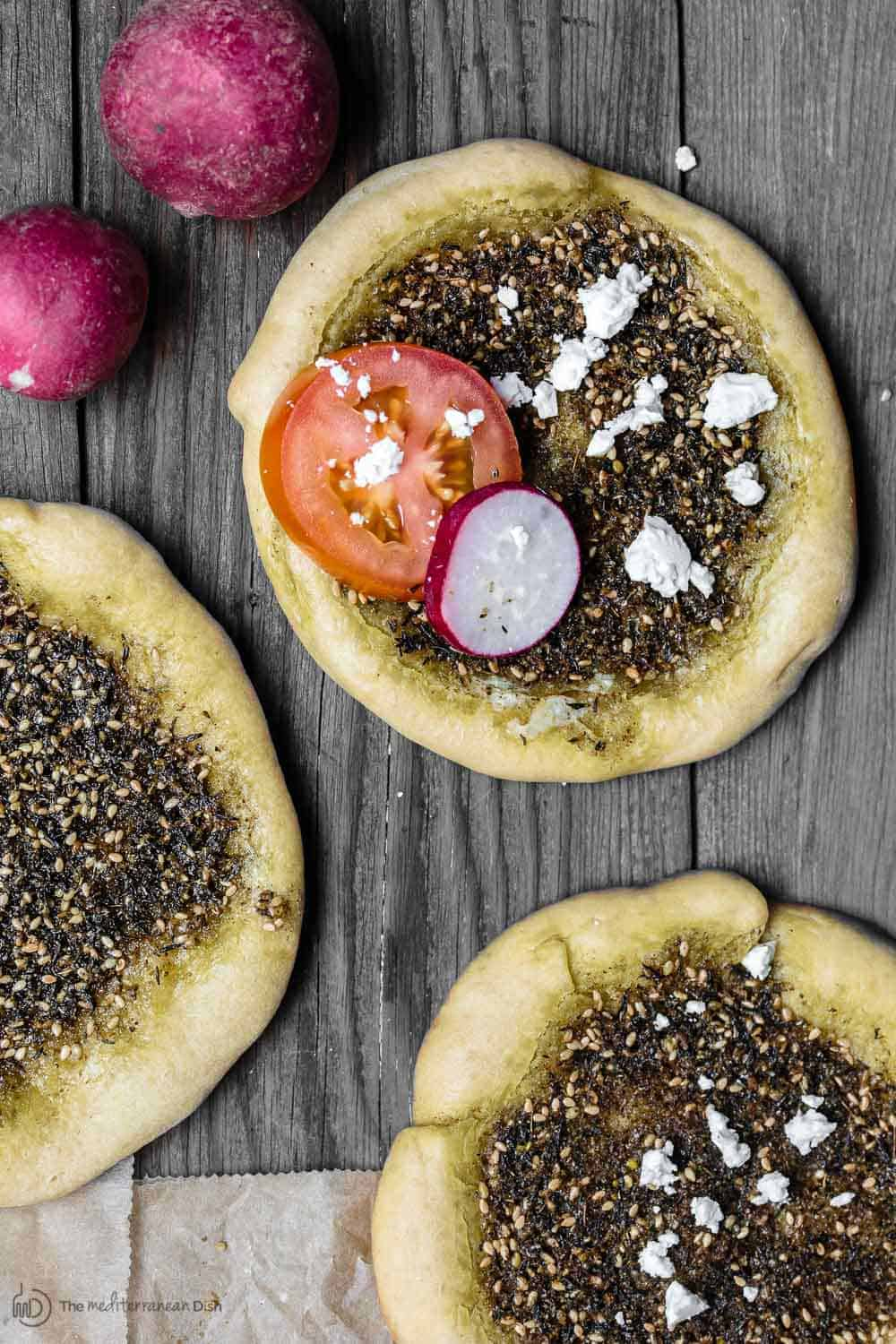 Za'atar Manaqish pastry garnished with cheese, tomato and radish