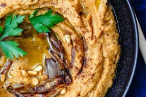 Bean Dip with Roasted Acorn Squash | The Mediterranean Dish. A rustic, flavor-packed white bean dip with a Mediterranean twist. I add caramelized shallots, warm Mediterranean spices, and toasted nuts! See the easy recipe on TheMediterraneanDish.com #beandip #whitebeandip #dip #appetizer #partyfood #holidayrecipe #squash #roastedsquash #hummus #mediterraneanrecipe #mediterraneandiet #mediterraneanfood