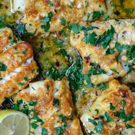 Baked cod in lemon and garlic sauce, garnished with parsley
