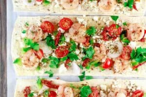 Mediterranean Shrimp Flatbread Pizza | The Mediterranean Dish. Easiest ever shrimp pizza on flatbread with Mediterranean favorites like feta, shallots, and sun-dried tomatoes. Takes less than 15 minutes start-to-finish! See the easy recipe on TheMediterraneanDish.com
