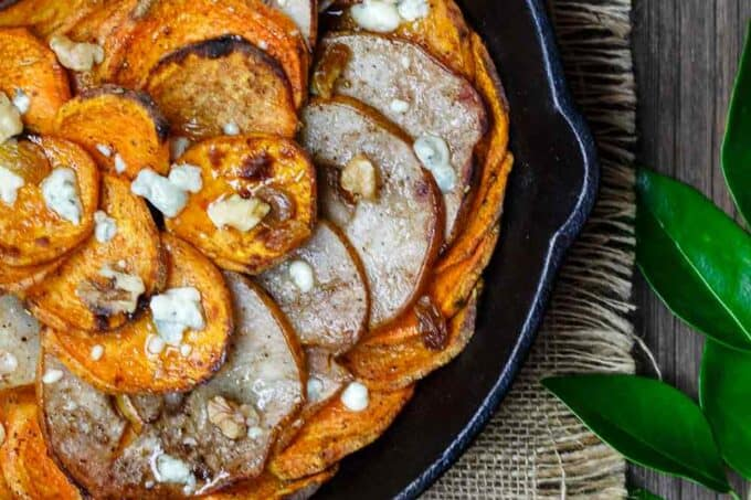 Roasted Pear and Sweet Potato Gratin | The Mediterranean Dish. A simple, rustic, and healthy sweet potato gratin (or sweet potato casserole). Perfectly seasoned then roasted to tender perfection. And the finishing touches of honey, cheese and nuts are not to be missed. See the easy recipe on TheMediterraneanDish.com #mediterraneanrecipe #mediterraneandiet #sweetpotatocasserole #sweetpotato #holidayrecipe #thanksgiving