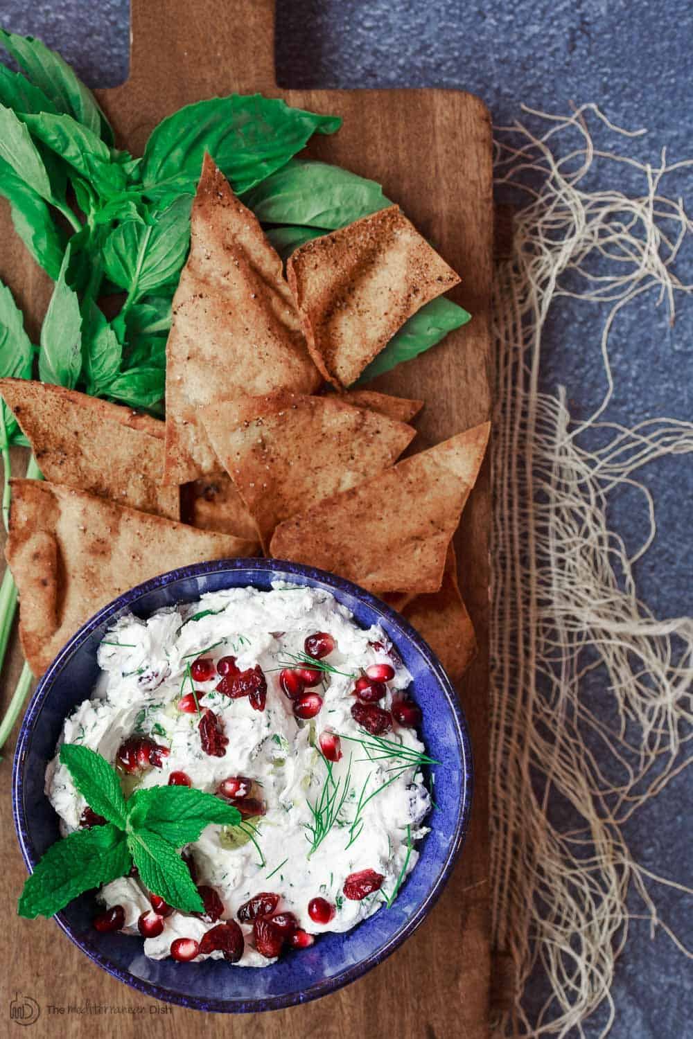 Cranberry and Herb Labneh Recipe | The Mediterranean Dish. Creamy labneh cheese makes the perfect Mediterranean party dip with loads of fresh herbs and dried cranberries. This labneh recipe comes with a homemade pita chips recipe as well! So easy. See it on TheMediterraneanDish.com