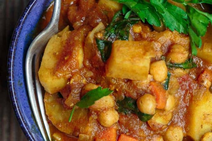 Moroccan Vegetable Tagine Recipe | The Mediterranean Dish. A simple and succulent vegetable stew, flavored Morrocan-style with warm spices, aromatics, and dried apricots. The best vegetable tagine or vegetable stew you'll have. See it on TheMediterraneanDish.com #vegetablestew #tagine #mediterraneanfood #moroccanfood #veganrecipe #onepot